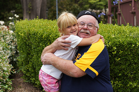 girl hugging her grandfather