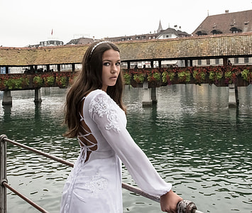 woman wearing white applique long-sleeved strappy-back dress holding gray metal railings near body of water