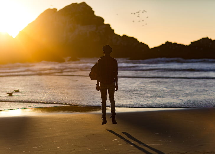 silhouette of man near seashore in front of mountain at daytime
