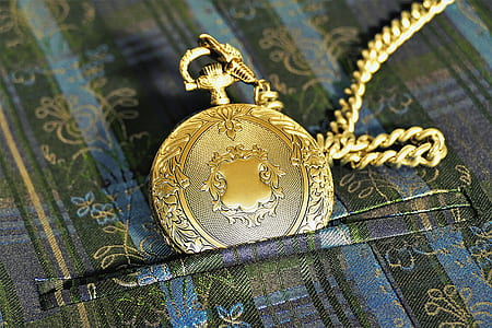 round gold-colored pocket watch