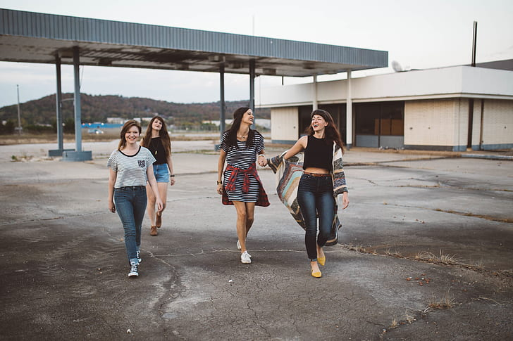 four woman walking down the street