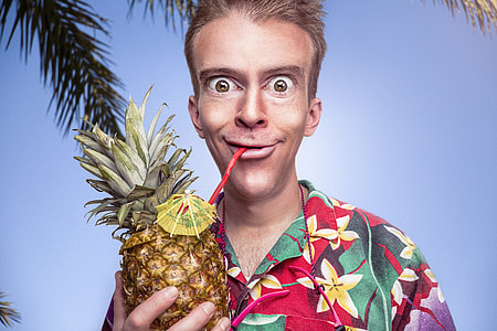 man in red, yellow, and green flora button-up shirt holding pineapple under blue sky
