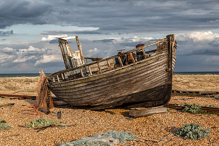 Wide-angle shot of an old abandoned fishing boat and nets. Image captured in Dungeness, Kent, England