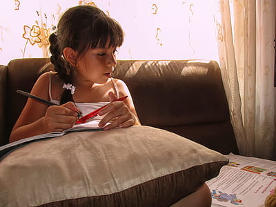 girl sitting while holding pen and notebook in room