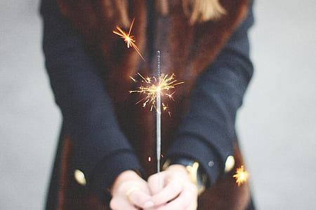 person's hand holding firecracke