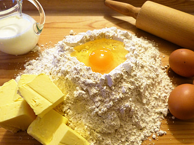 egg in flour beside rolling pin and clear glass pitcher