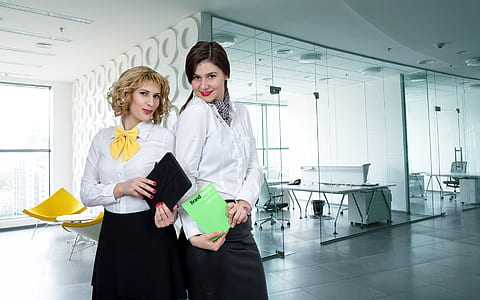 two women in white button-up long-sleeved collared shirts inside room