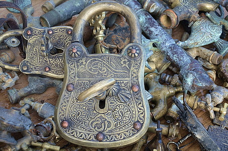 vintage brass-colored padlock with key on faucet with pipes