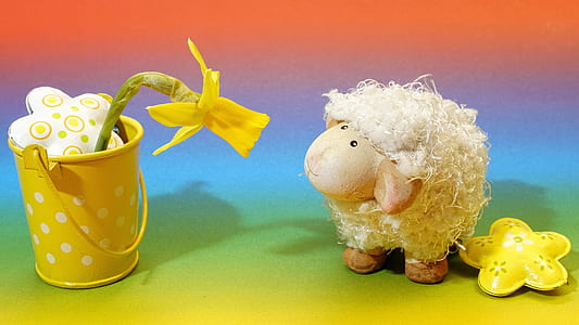 sheep plush toy looking at yellow artificial flower on steel pot