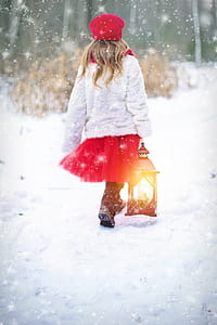 girl wearing white sweater and red tutu skirt walking on snow covered ground holding lantern