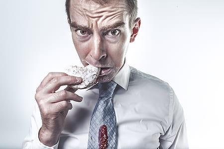 man wearing gray dress shirt eating a cookie