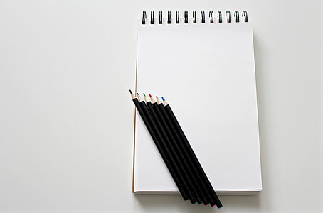 five assorted-color color pens on white spiral notebook