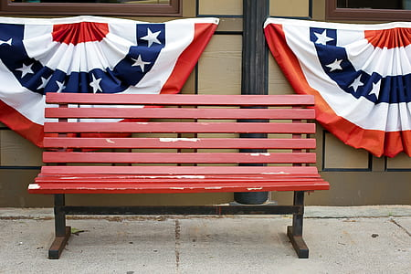 red wooden bench beside brown wall two flags