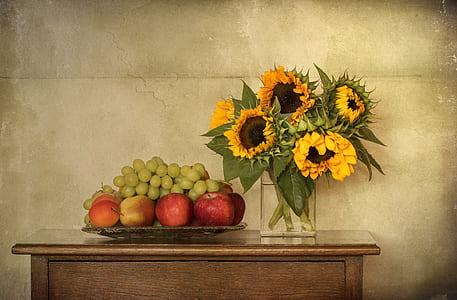 sunflower arrangement near bunch of fruits on brown wooden table