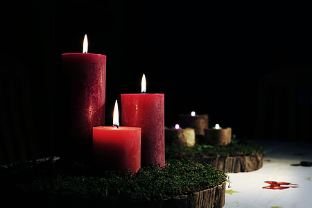 three lighted red pillar candles