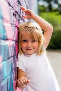 girl wearing white shirt lean on printed wall