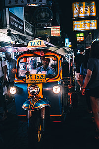 man riding blue and yellow auto rickshaw
