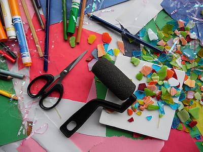 black paint roller beside black scissors and colored pencils