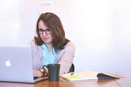 woman wearing gray open cardigan using silver MacBook
