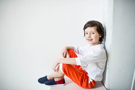 boy wearing white long-sleeved shirt and red pants