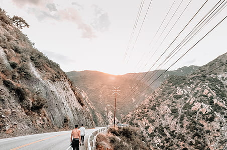 photo of two people walking on concrete road towards mountains