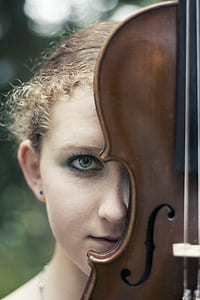 shallow focus photography of woman face with violin