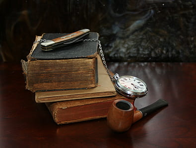 brown and black wooden pipe near books and pocket watch