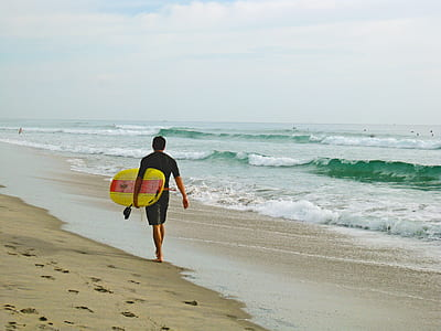 man in black shirt and shorts carrying a yellow surfboard on beach