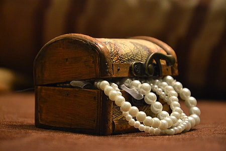 white pearl necklace in brown wooden dome chest