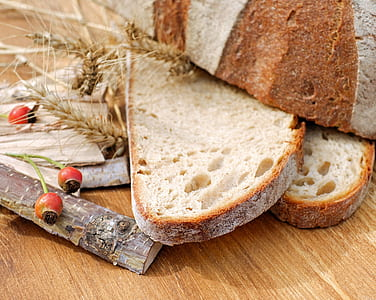 sliced bread beside wood sticks on brown wooden surface