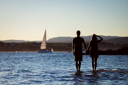 man and woman standing on body of water
