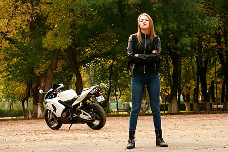 woman wearing black leather zip-up jacket with motorcycle
