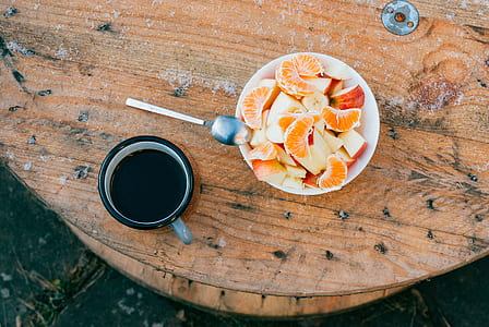 sliced oranges and apples inside round white ceramic bowl with silver spoon on top beside black ceramic mug