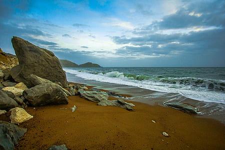 brown boulders on seashore under cloudy sky