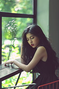 woman in black sleeveless dress sitting near window