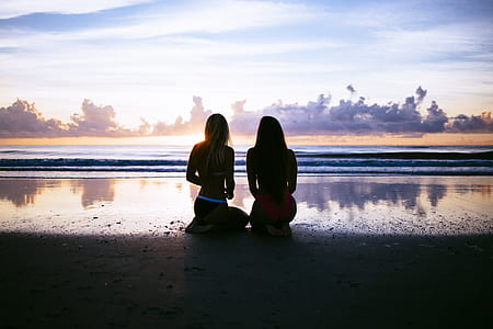 silhouette of two women sitting at seashore