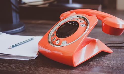 orange rotary telephone near the paper