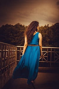 woman wearing blue sleeveless maxi dress
