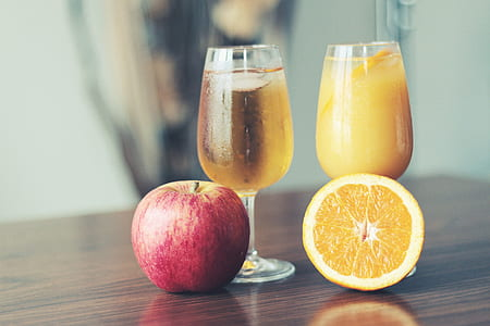 apple and sliced orange beside two clear wine glasses