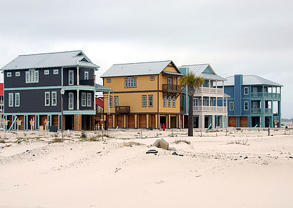black, brown, and blue painted houses on brown sand under blue sky during daytime