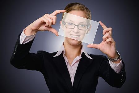 woman wearing black framed eyeglasses and black blazer holding glass panel