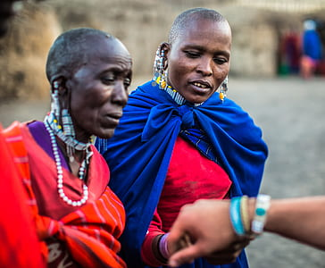 Two Woman Looking on Persons Bracelet