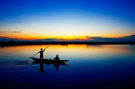 silhouette photography of two people on boat