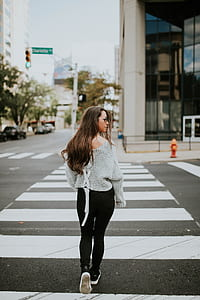 woman in gray sweater and black pants on pedestrian crossing during daytime