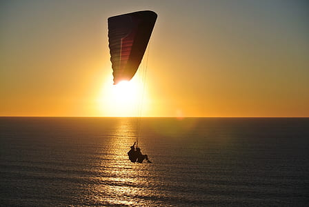 paragliding of two person above water during dusk