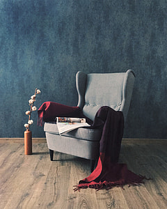 gray padded wing chair with red scarf on top