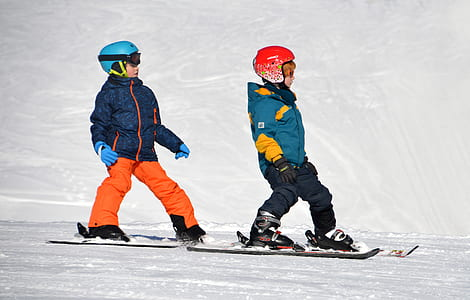photography of children riding snowboards