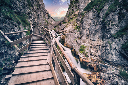 brown wooden footbridge between gray rocky mountain