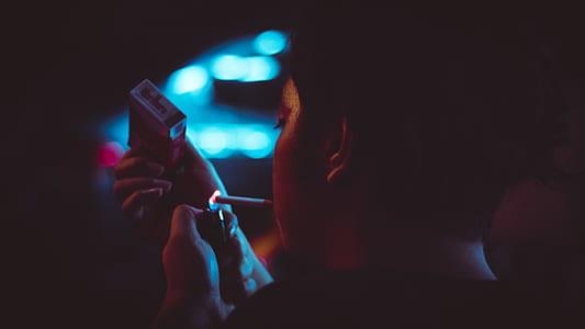 Man Lighting Up a Cigarette during Nighttime in Tilt Shift Lens Photograhy