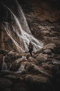 photo of man wearing brown jacket near waterfalls